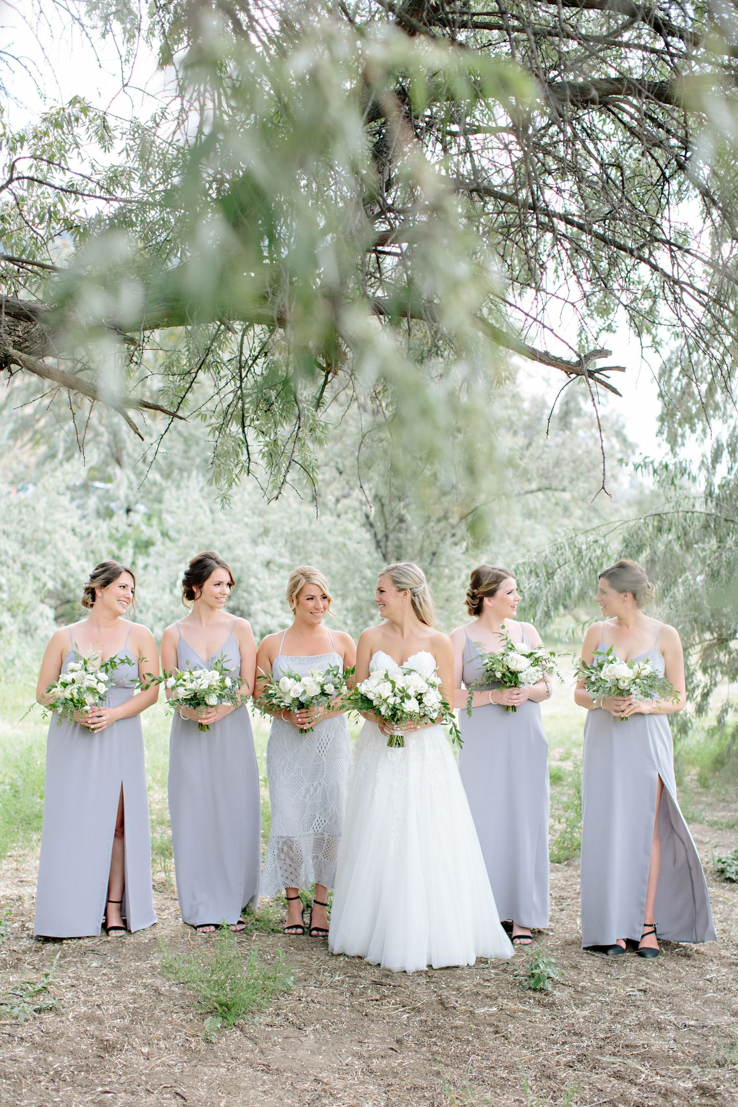 bride and bridesmaid walking under olive tree