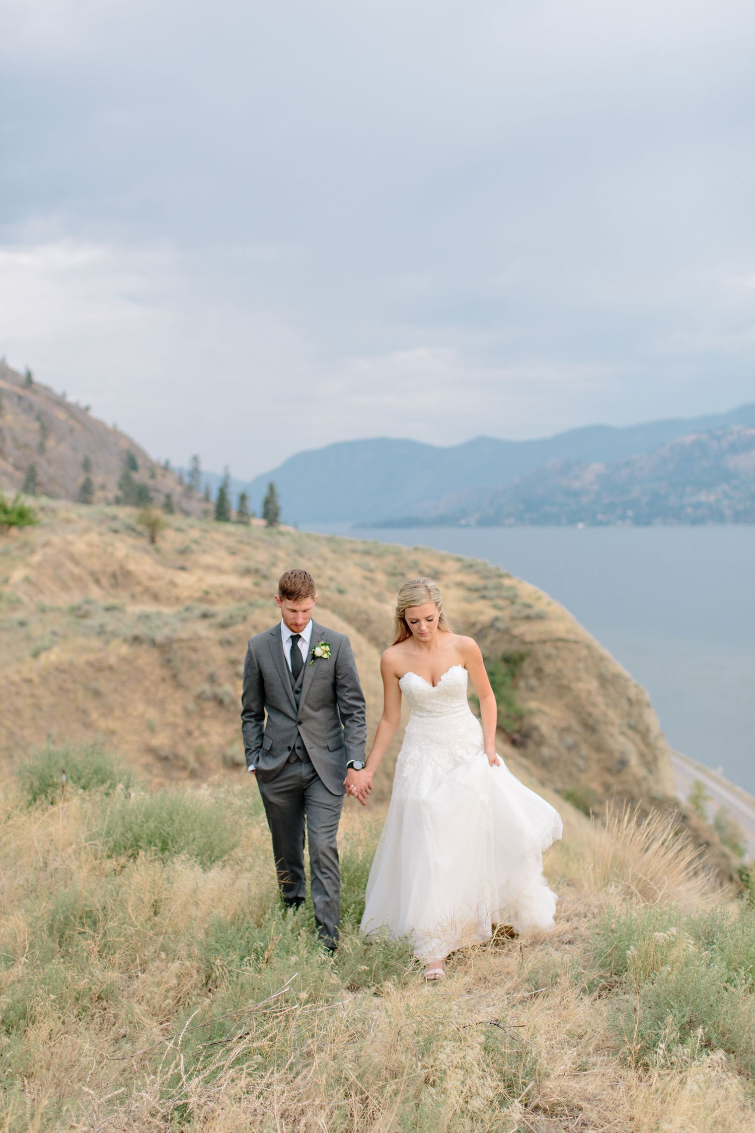 bride and groom walking on cliff edge