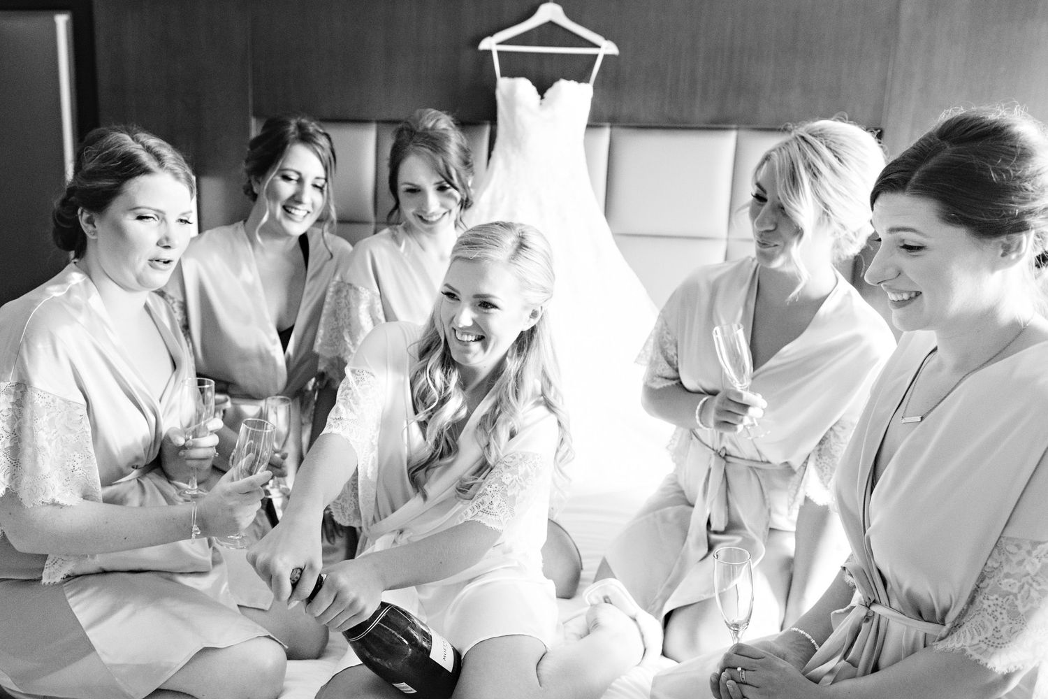 bride and bridesmaids opening champagne