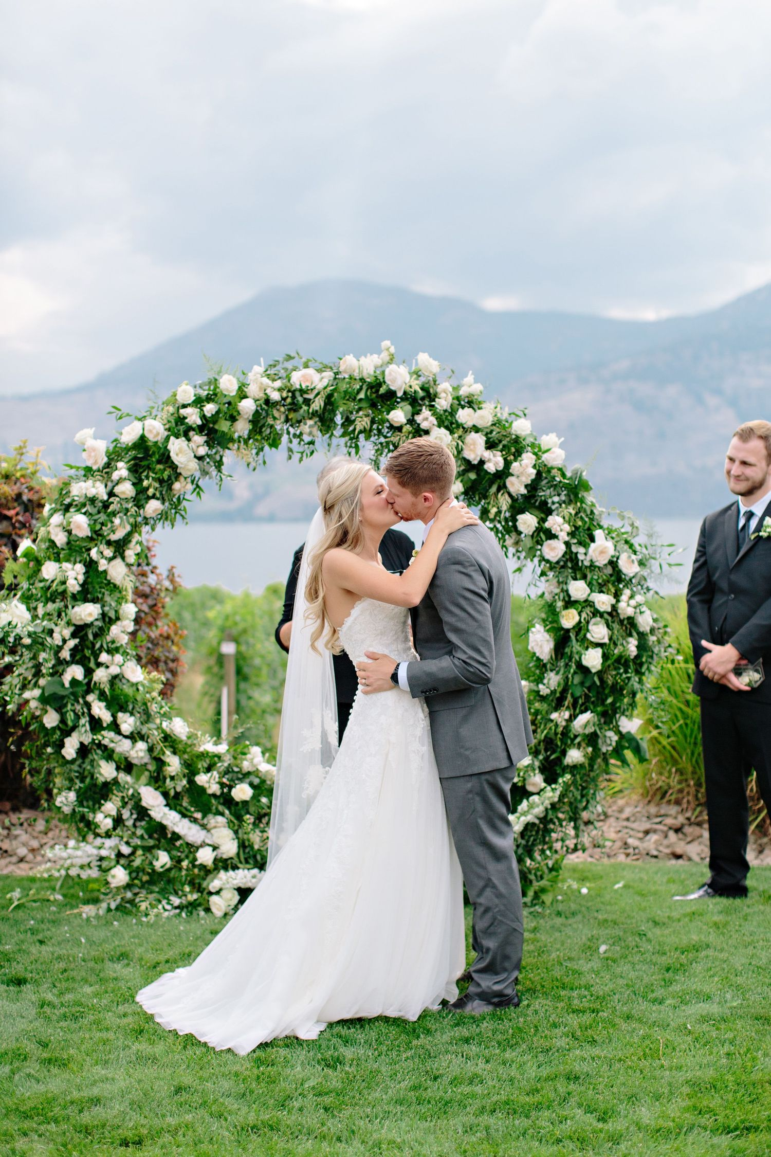 first kiss with round arch with white roses and greenery
