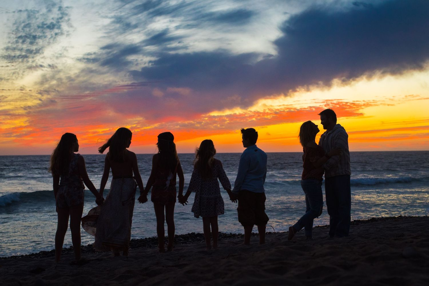 Photo of a family on the beach at sunset in San Clemente, California