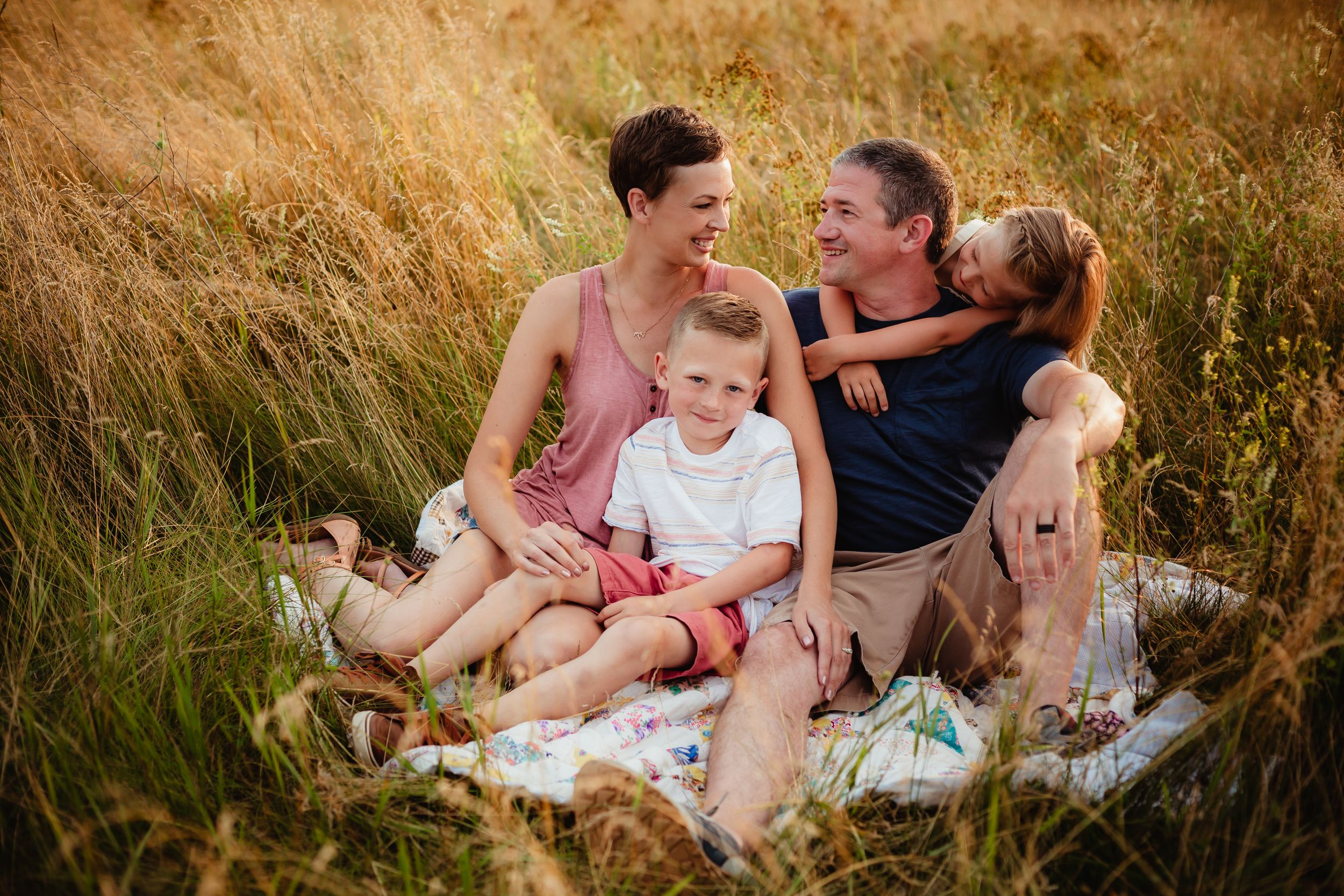 A mom, dad, brother, and sister sitting in a gold and green field. They are embracing and smiling.