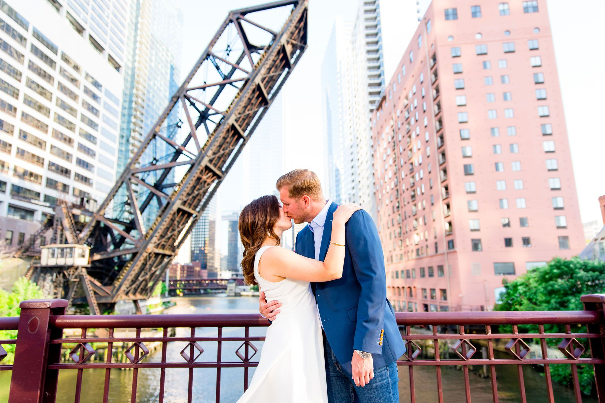 man in navy suit and woman in white dress kissing in front of Chicago River for sunset engagement pictures in Chicago