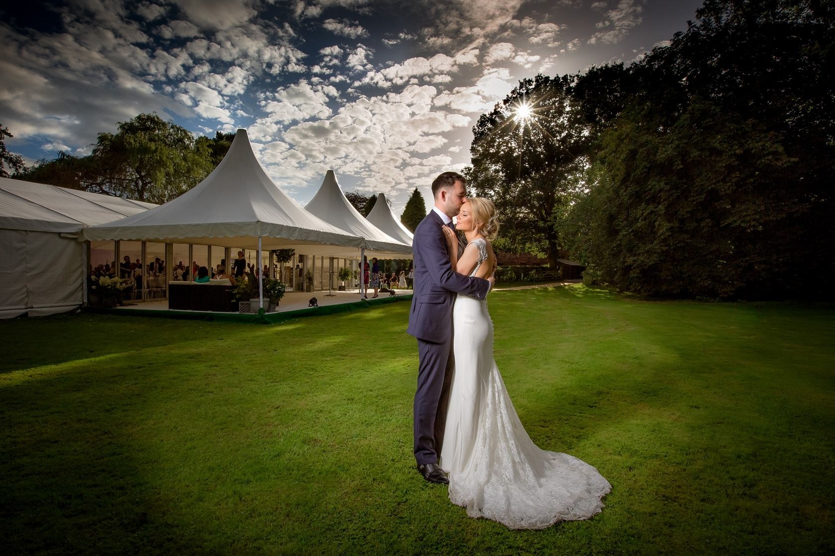 Groom holds his bride in her white wedding dress on a Summer evening outside their wedding marquee in a Cheshire garden