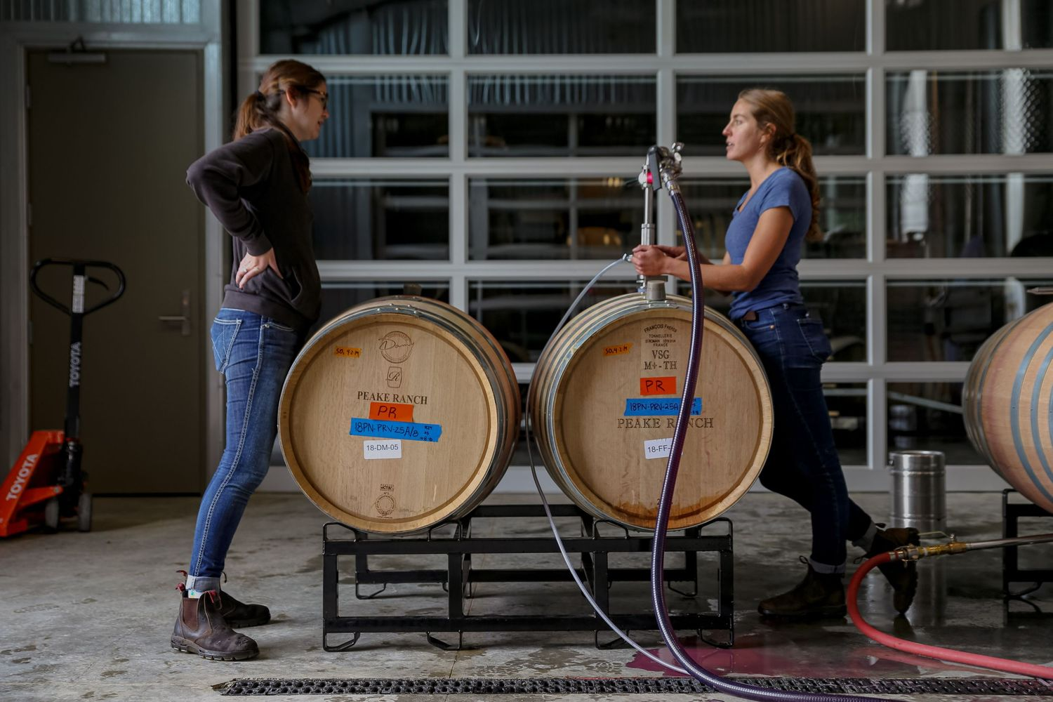 Women winemaker portraits.  Winemaker Wynne and Assistant Winemaker Lauren talking while racking wine at Peake Ranch.