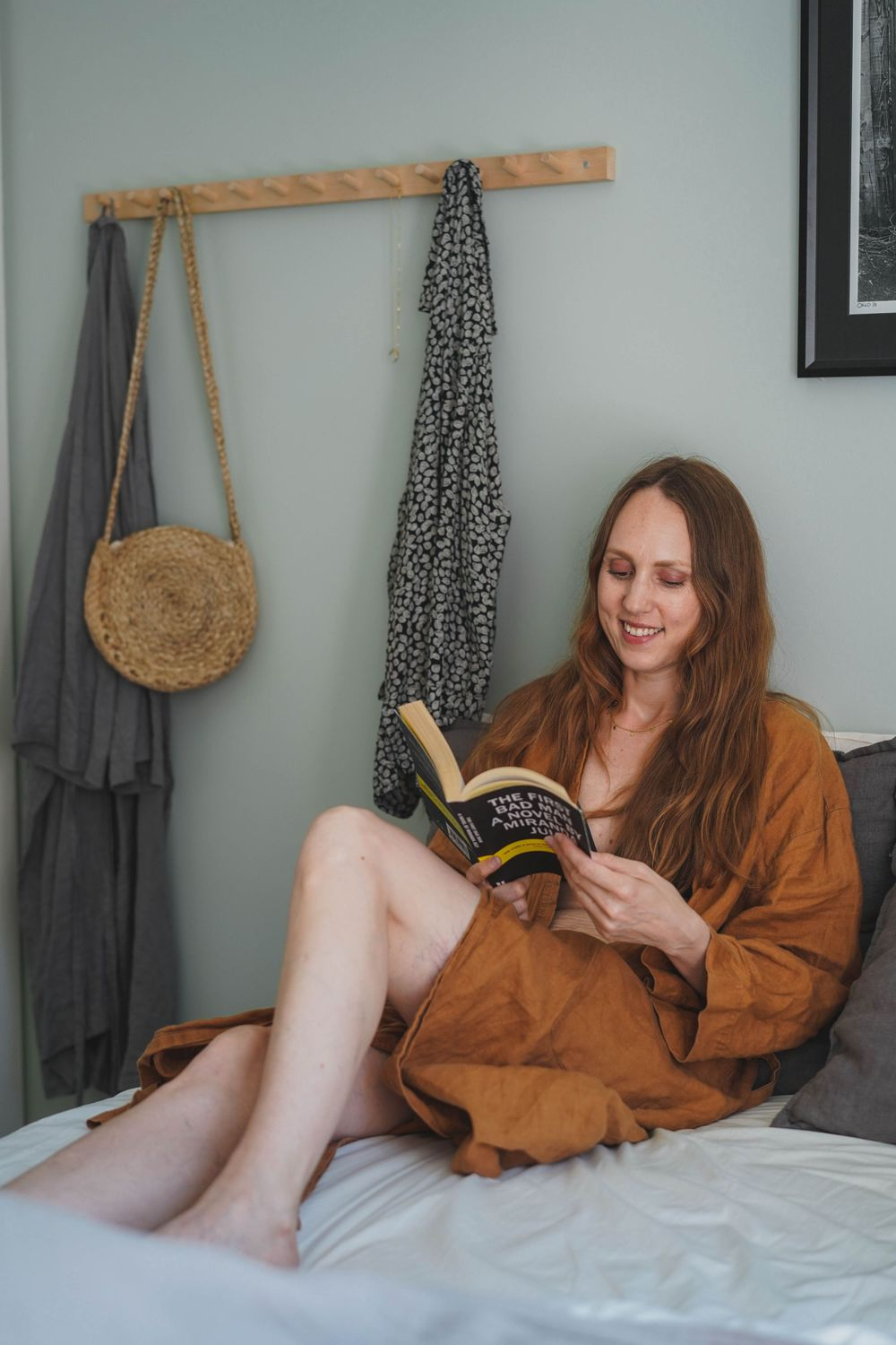 woman in a brown bathrobe lying on a bed and reading a book