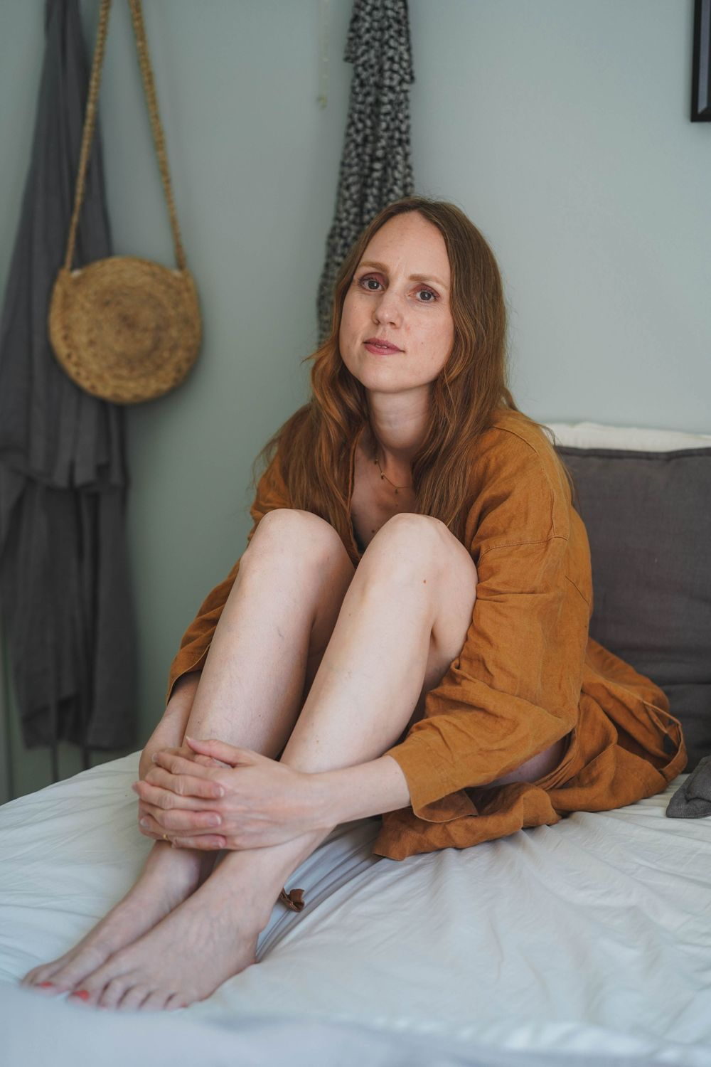 woman in a brown bathrobe sitting on a bed