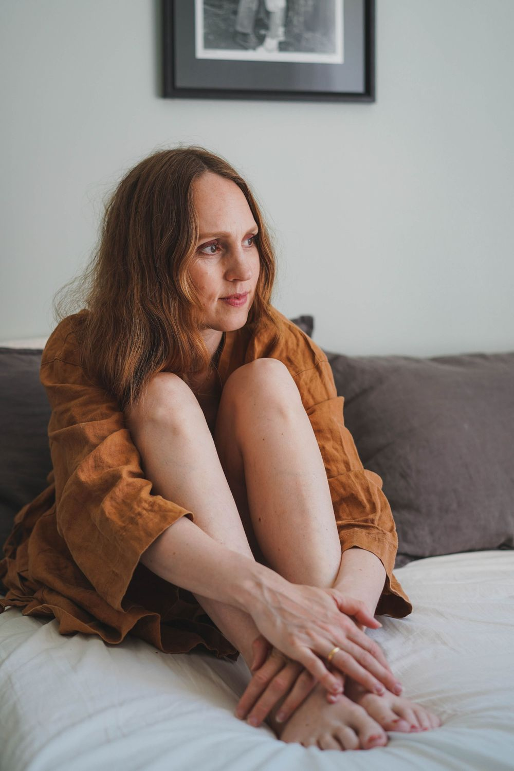 woman in a brown bathrobe sitting on the bed
