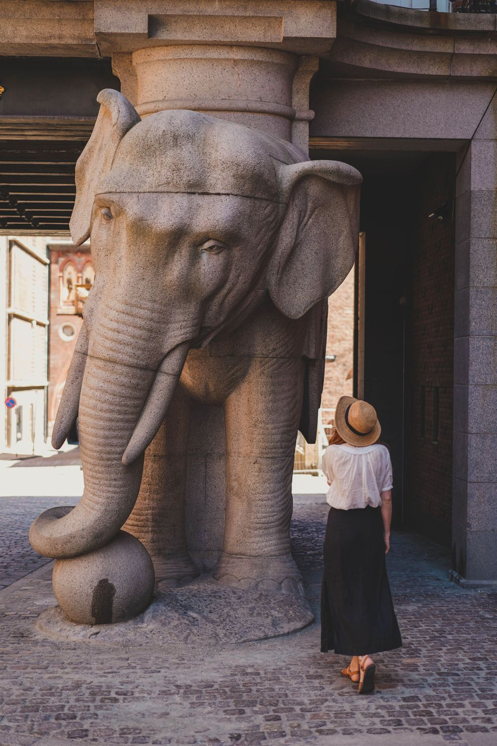 wonam in a white shirt and a straw hat looking at the giant elephant statue