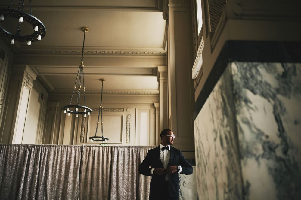 groom getting ready on wedding day in Kansas City Union Station ballroom, buttoning jacket