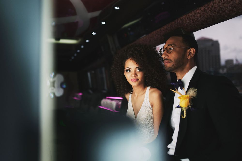 bride and groom sit in limo on their wedding day