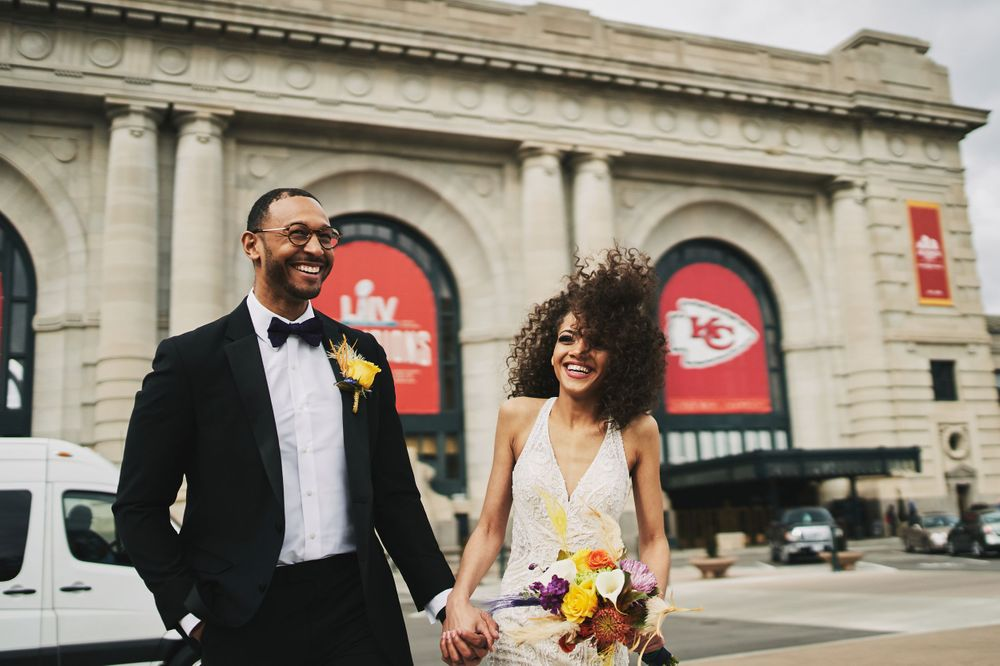 bride and groom walk hand in hand outside of Union Station in Kansas City