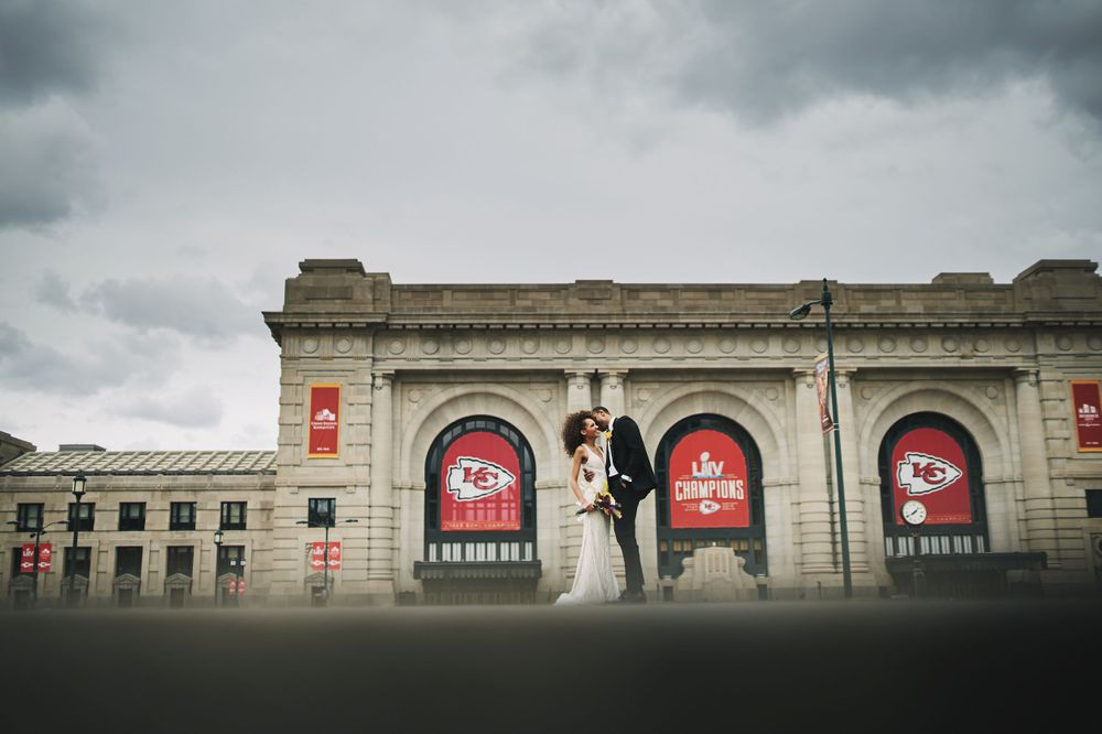 wide angle photo of bride and groom kissing in front of Kansas City Union Station and KC Chiefs signs