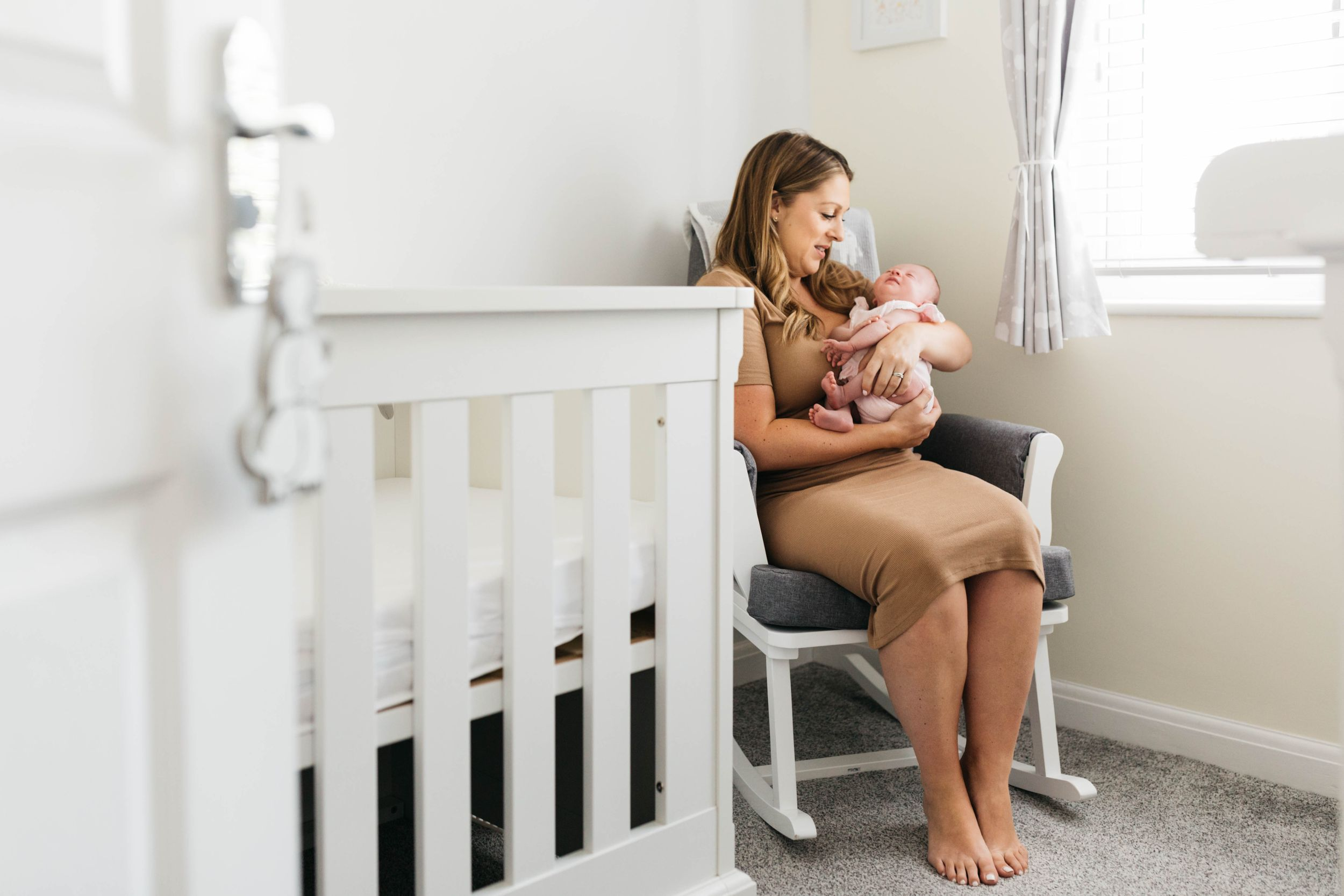 mum sitting in rocking in baby room holding newborn daughter