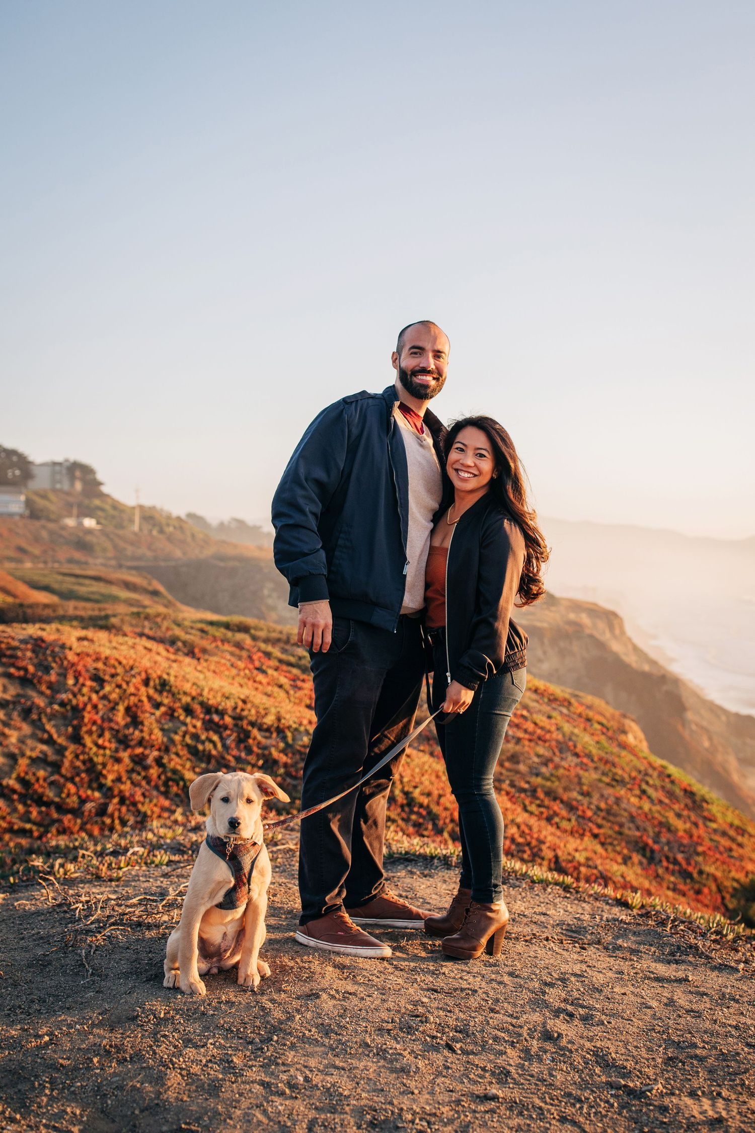 A couple stands with their dog during their engagement photoshoot in Pacifica, California.
