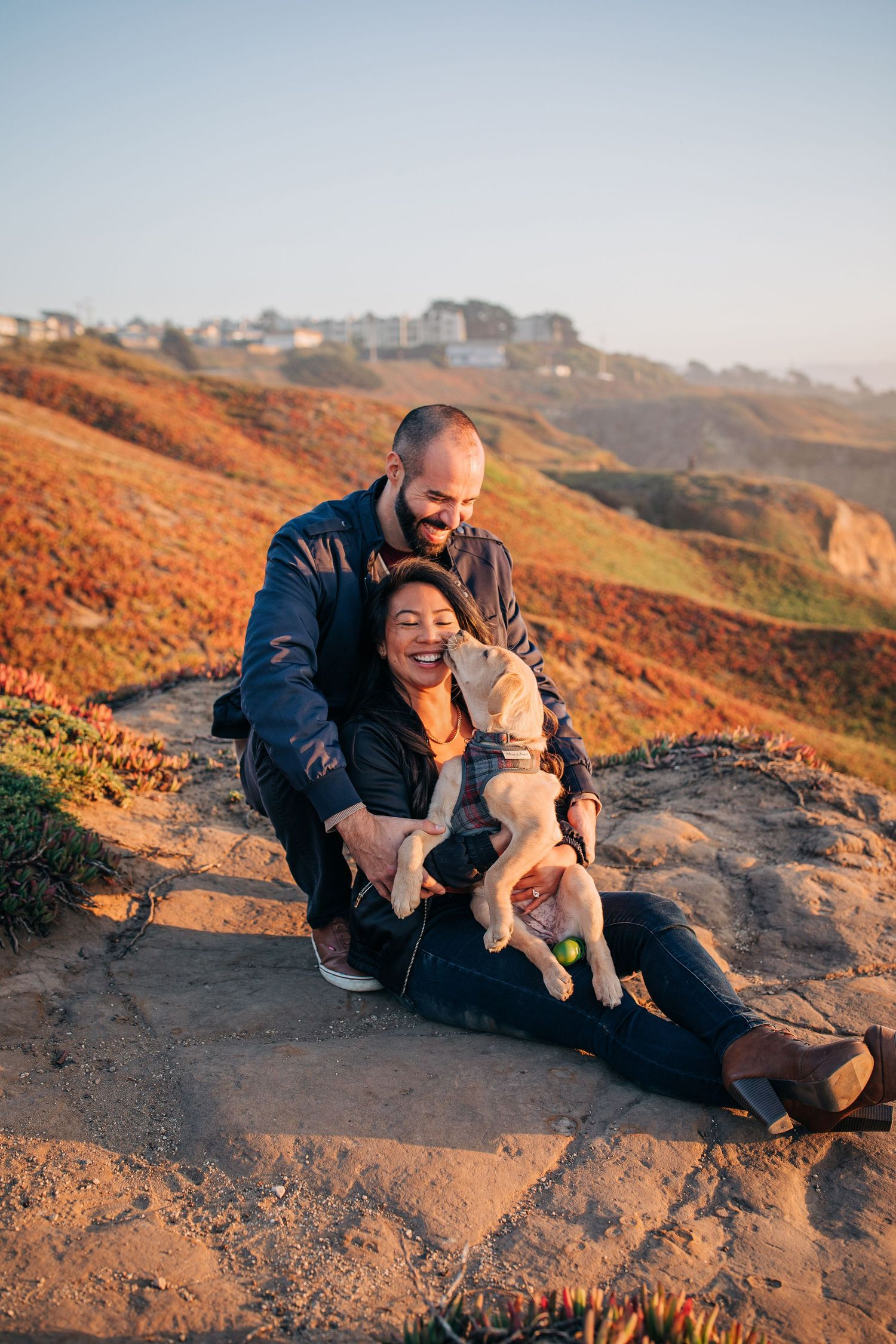 A couple sits with their dog at Mussel Rock Park Beach in California during their engagement photoshoot.