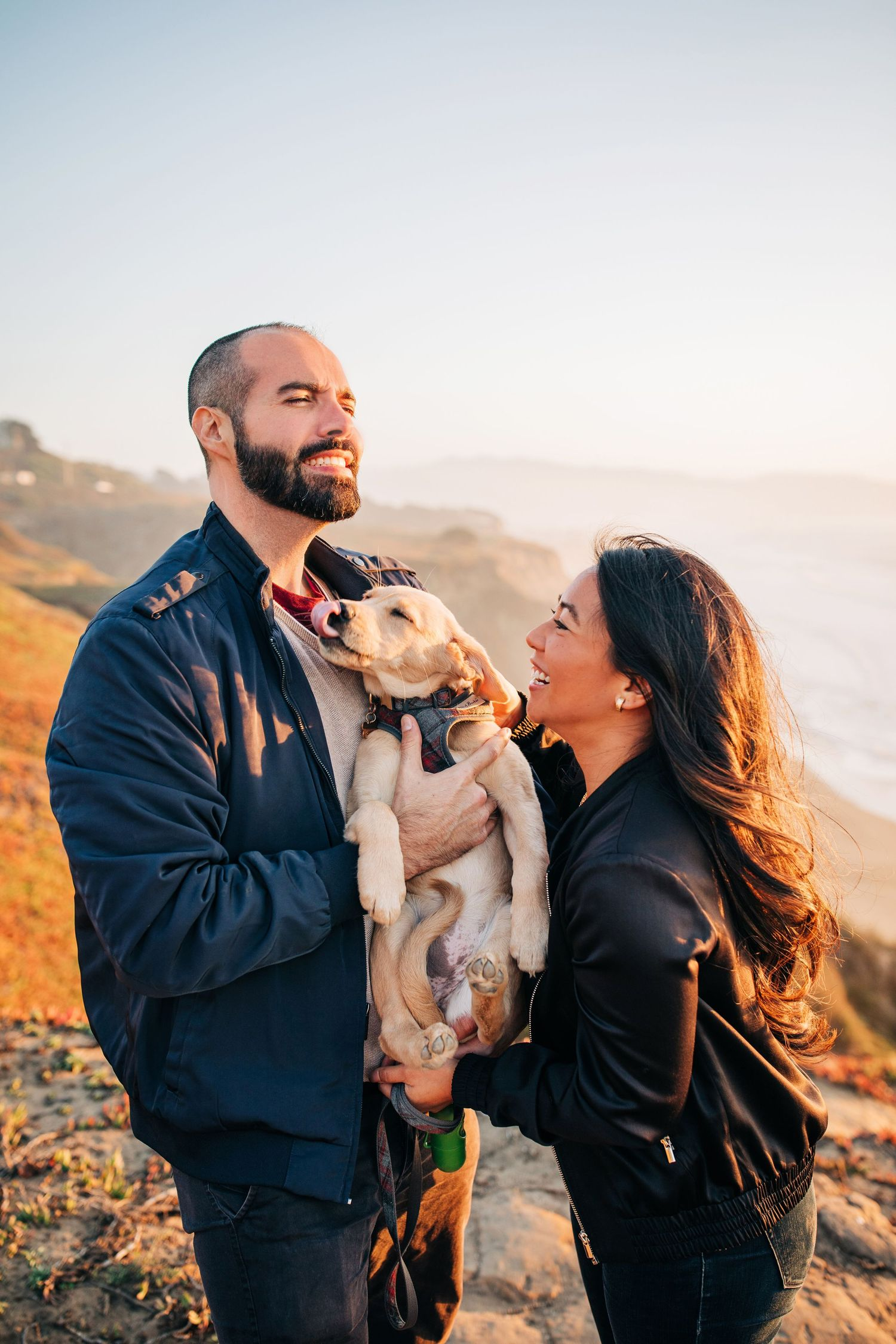 A couple laughs while holding their dog at Mussel Rock Park Beach in California during their engagement shoot.