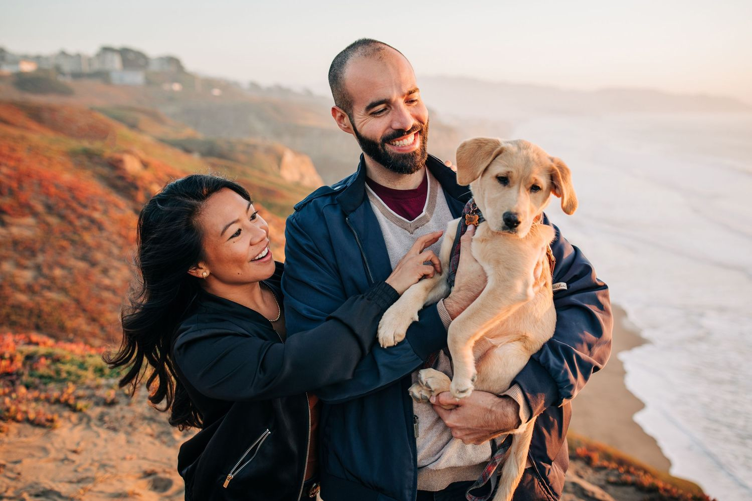 A couple poses with their dog at Mussel Rock Park Beach in California during their engagement shoot.