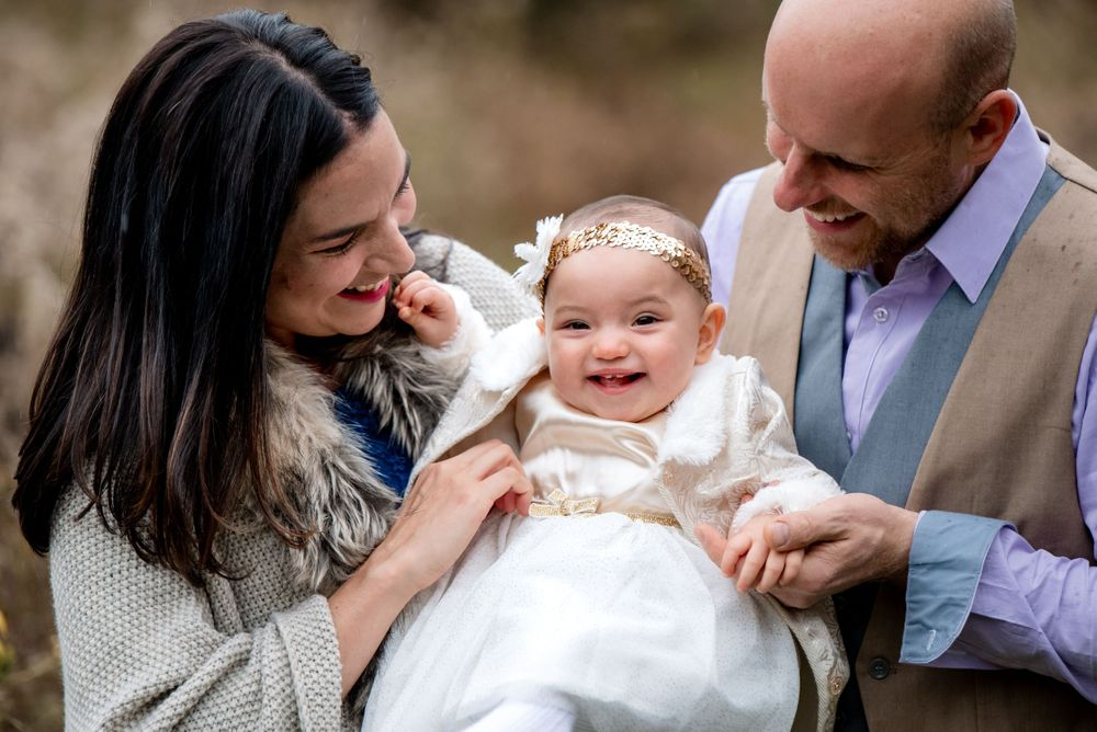 mom dad and baby during fall family session baby wearing white mom with dark hair everyone smiling looking at baby