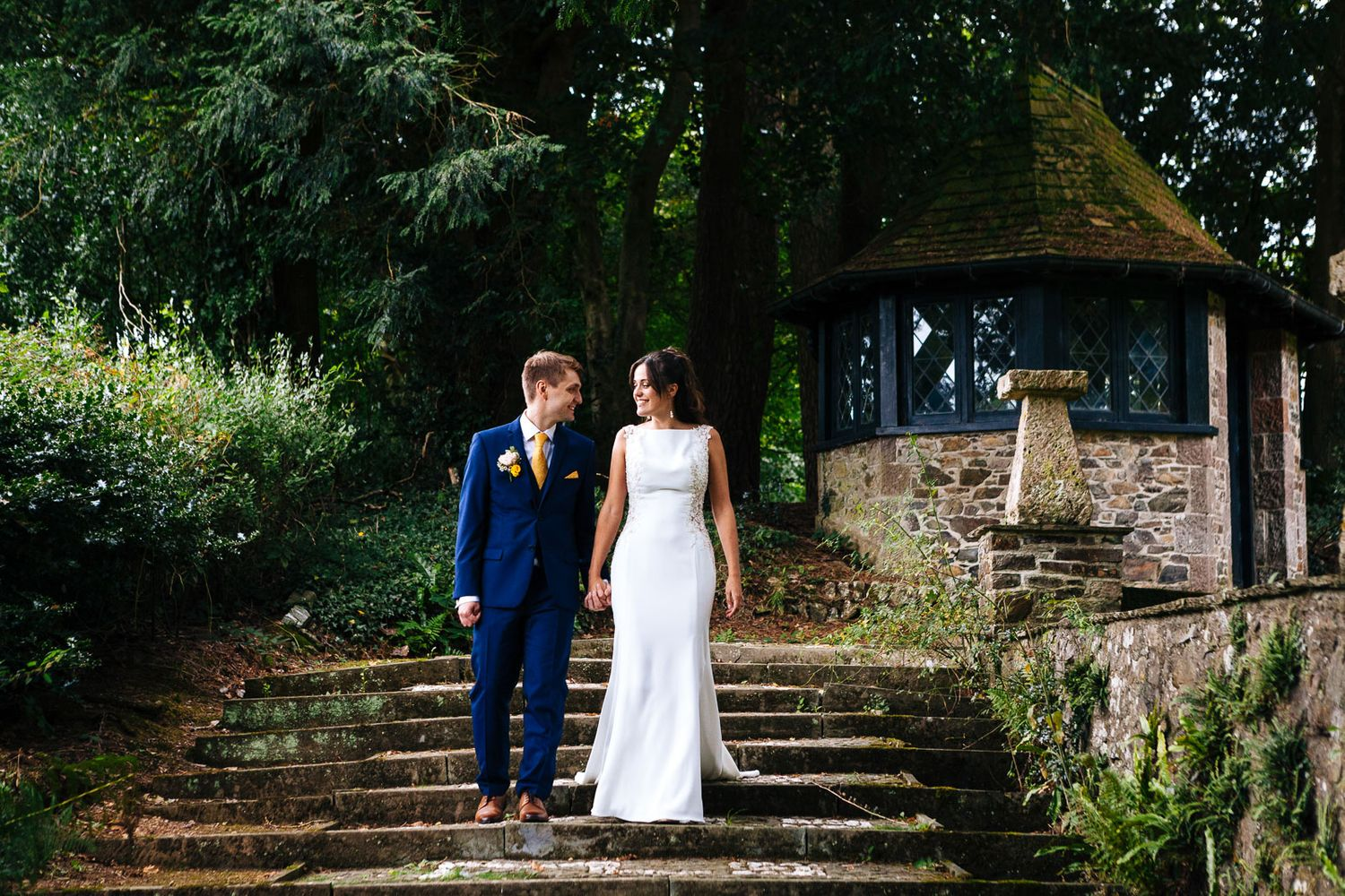 bride and groom walk down stairs at Coombe Trenchard Dartmoor wedding