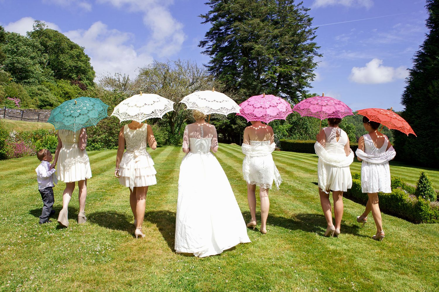 bridesmaids with parasols at summer wedding at Buckland Tout Saints