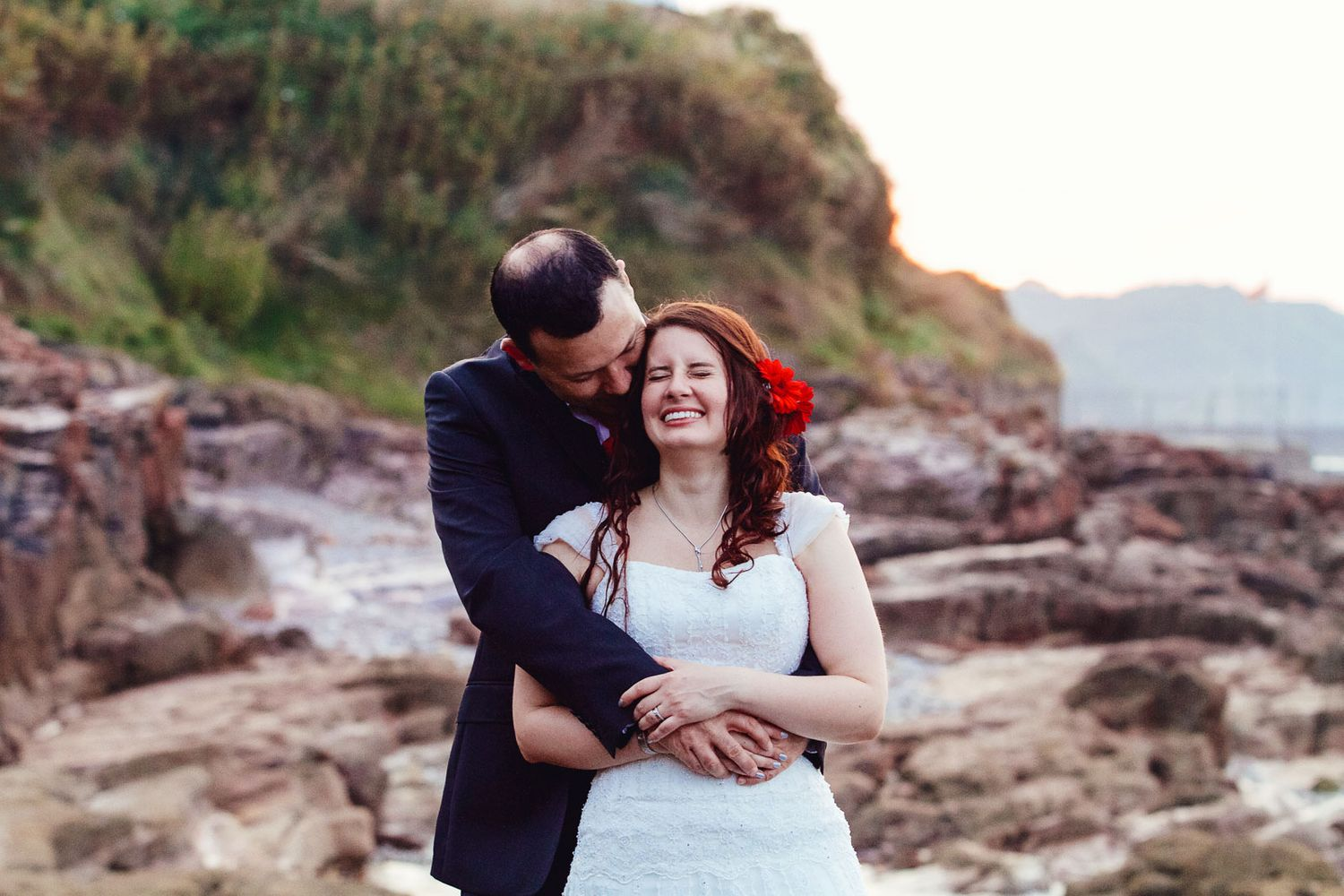 bride and groom at sunset on coast of Brixham Devon by wedding photographer Elizabeth Armitage