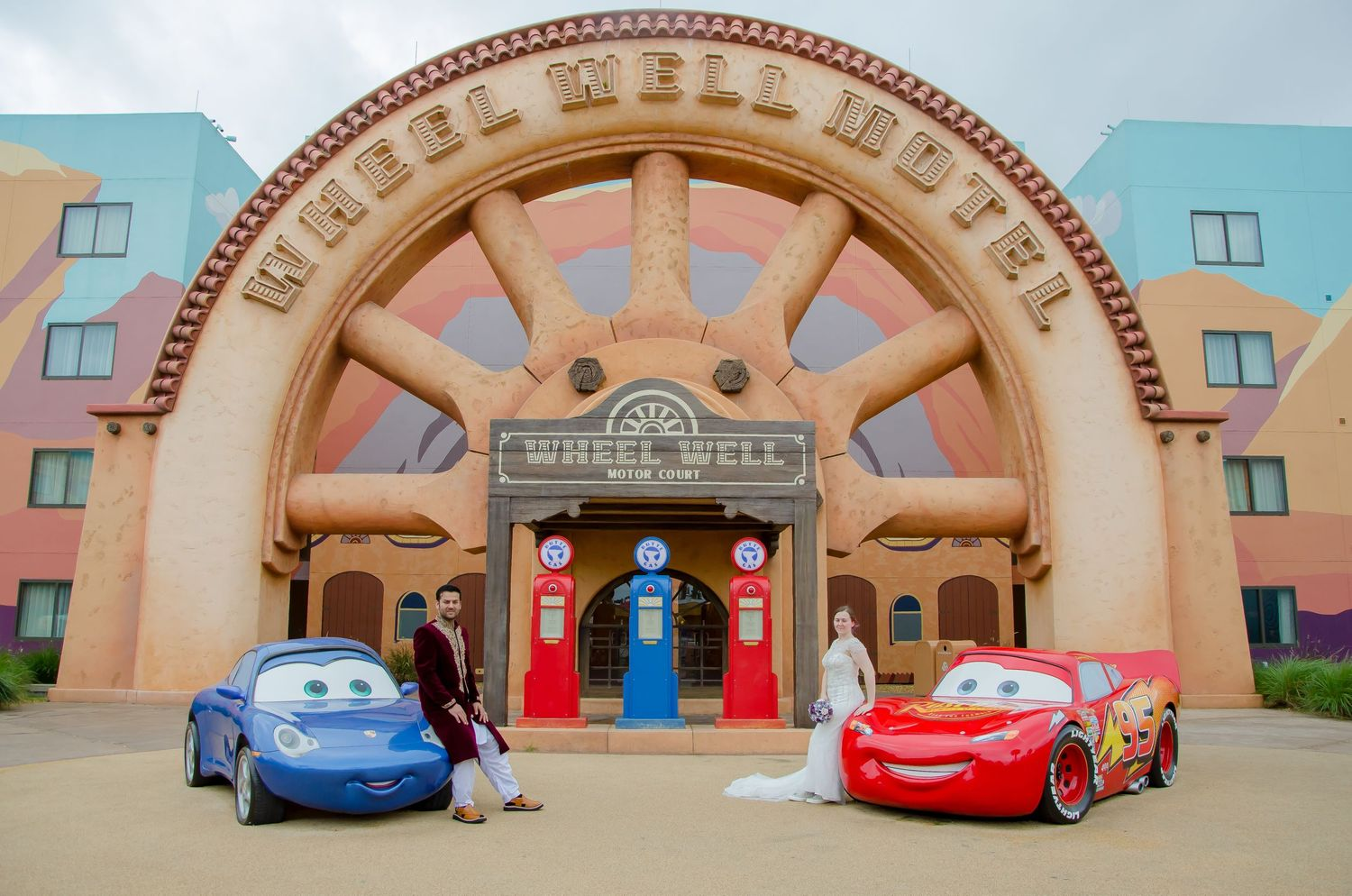 Bride and Groom with Sally and Lightning McQueen at their Walt Disney World Art of Animation wedding