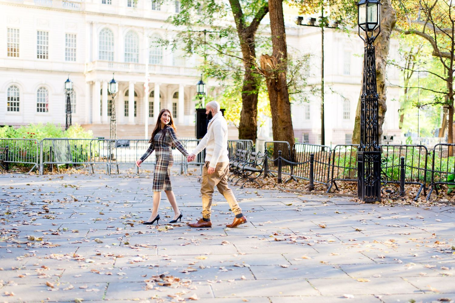 woman in plaid dress leads man in white sweater by hand at NYC City Hall in the fall