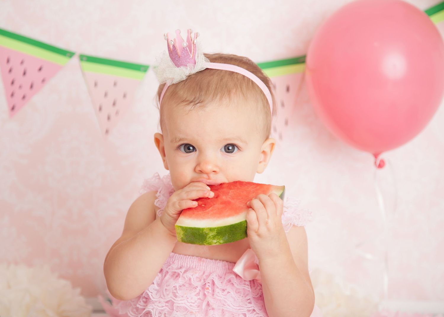 baby eating watermelon during cake smash photos