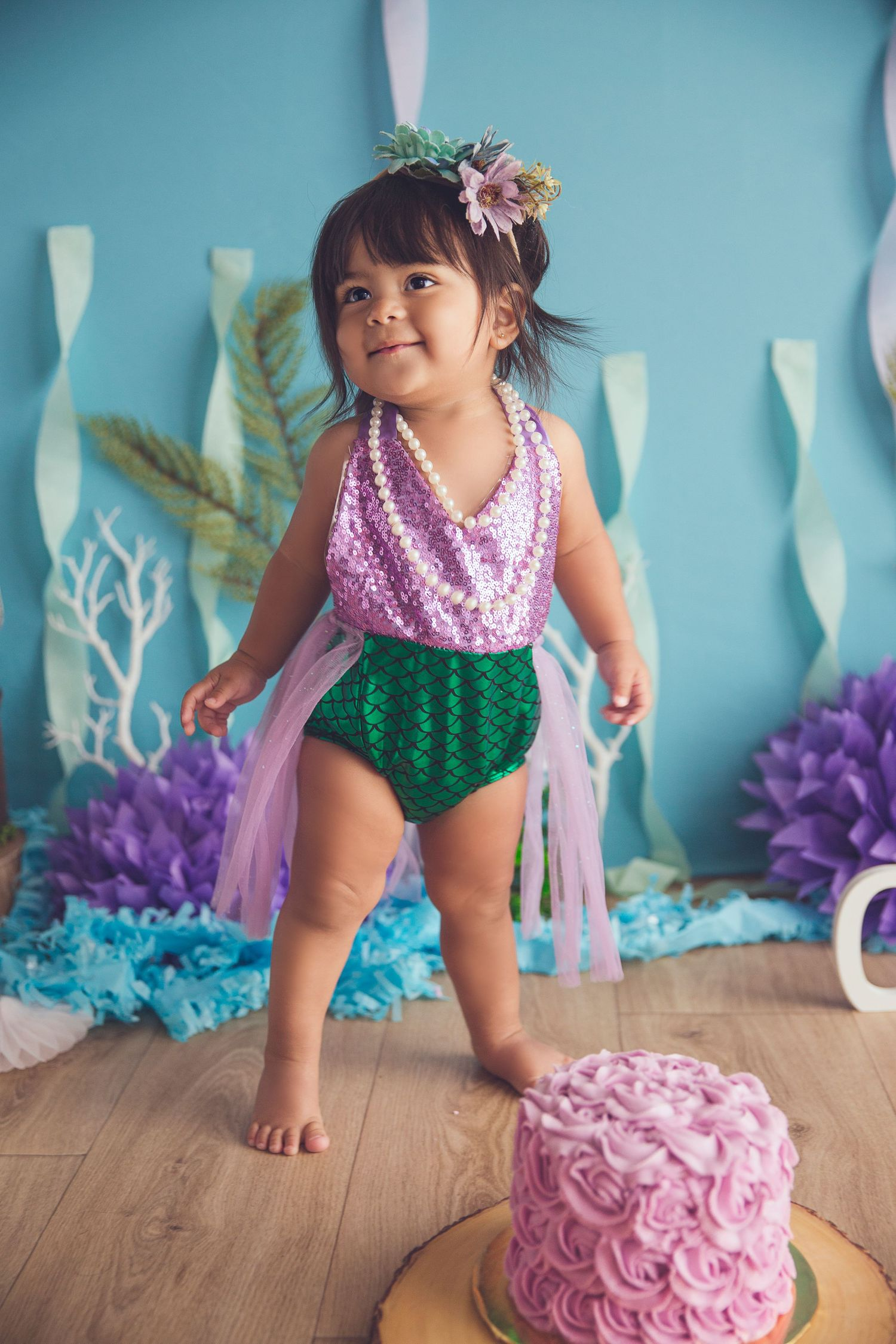 baby girl standing up in mermaid clothing and cake
