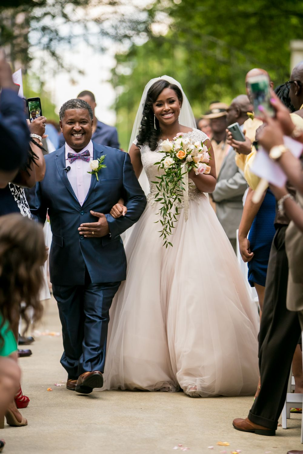 Jamil'ya and her father walk down the aisle during her wedding at the Lace House in Columbia, SC.  Photo by Jeff Blake