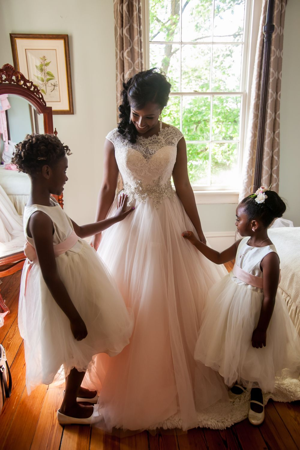 Flower girls look at bride Jamil'ya's dress before her before her wedding ceremony at the Lace House in Columbia, SC