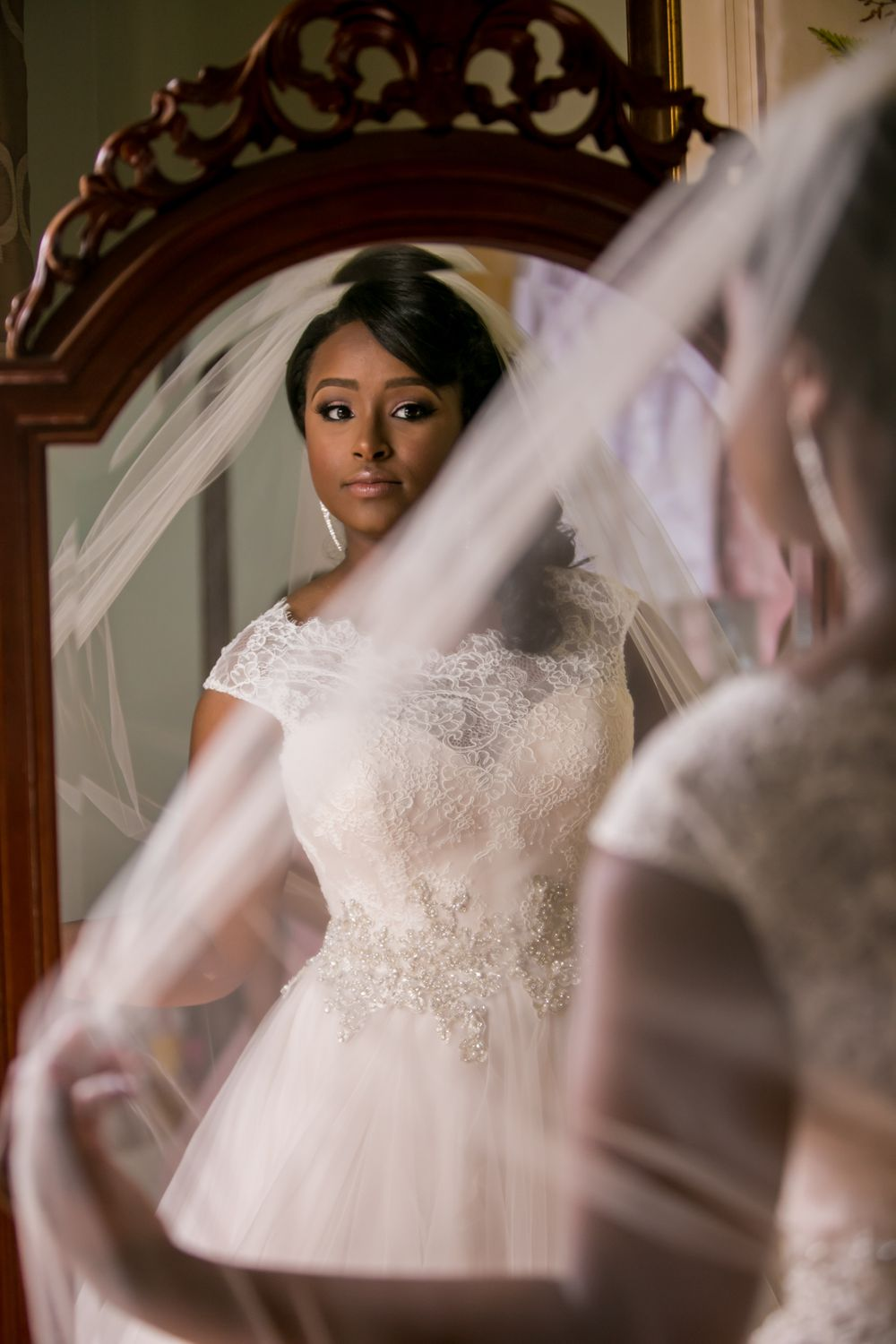 Bride Jamil'ya looks in the mirror before her wedding ceremony at the Lace House in Columbia, SC
