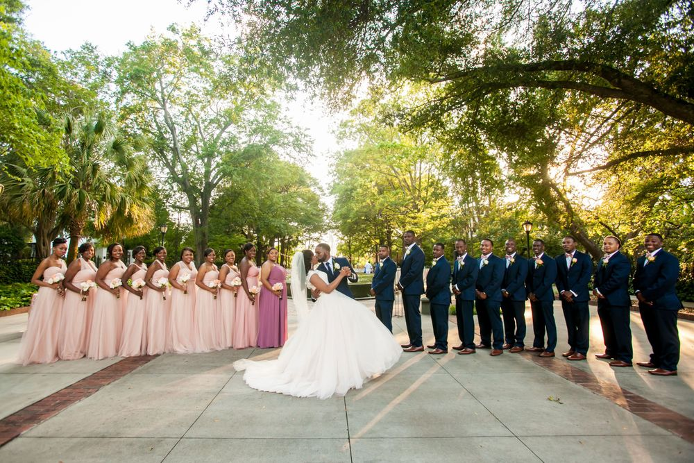 Bride and groom kiss with their wedding party following their wedding ceremony at the Lace House in Columbia, SC