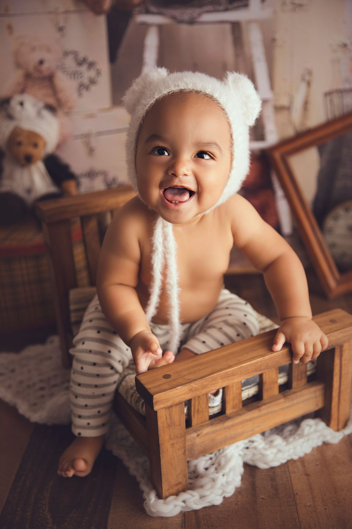 smiling 7 month old boy with bear bonnet sitting on wood bed