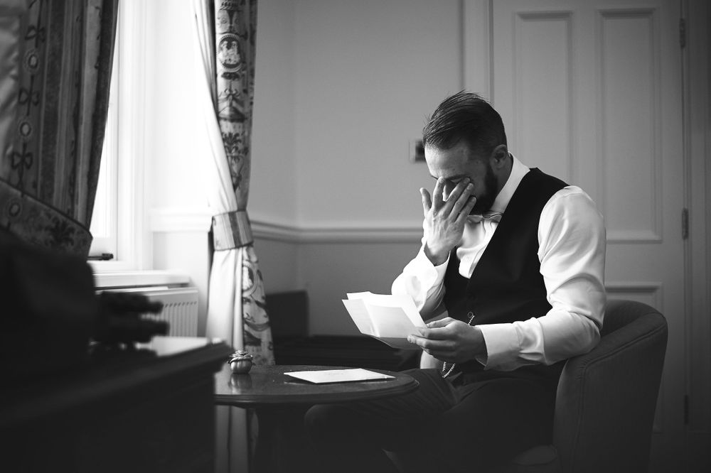 groom reads letter from bride before wedding at Lynford Hall, Norfolk. by Norfolk wedding photographer Faye Amare