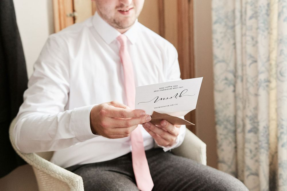 groom reads letter from bride before wedding at Old buckingham, Norfolk. by Norfolk wedding photographer Faye Amare
