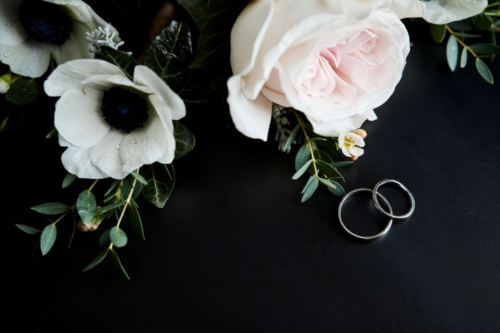bride and grooms rings with button holes flaylay by Norfolk Wedding Photographer Faye Amare