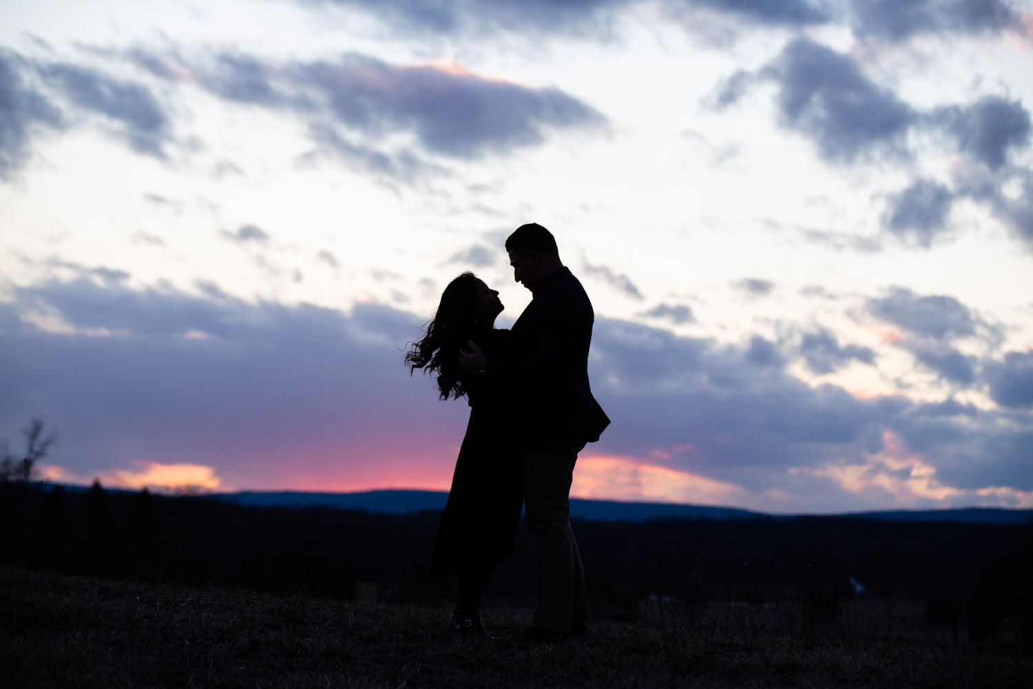 Engaged couple with sunset backdrop