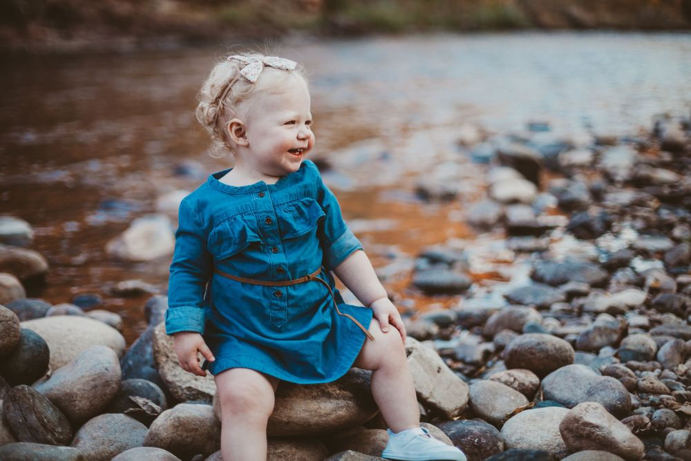 A baby poses for a photo at Watson Lake Natural Area in Fort Collins, Colorado during a Family Photography Session.