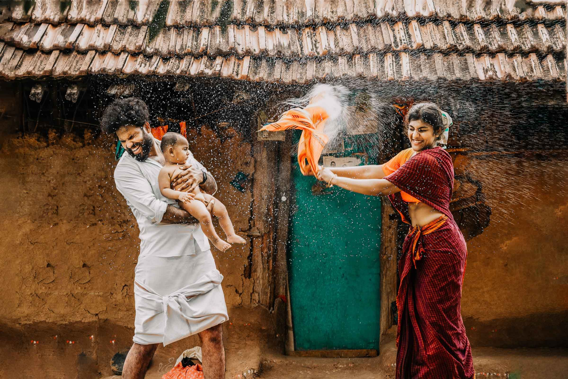 Creative village theme family portrait of a couple with their one month old baby boy captured by top baby photographer