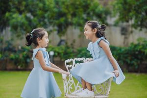 Twin baby girl kissing her twin sister while little vows is doing a kids photography session by little vows