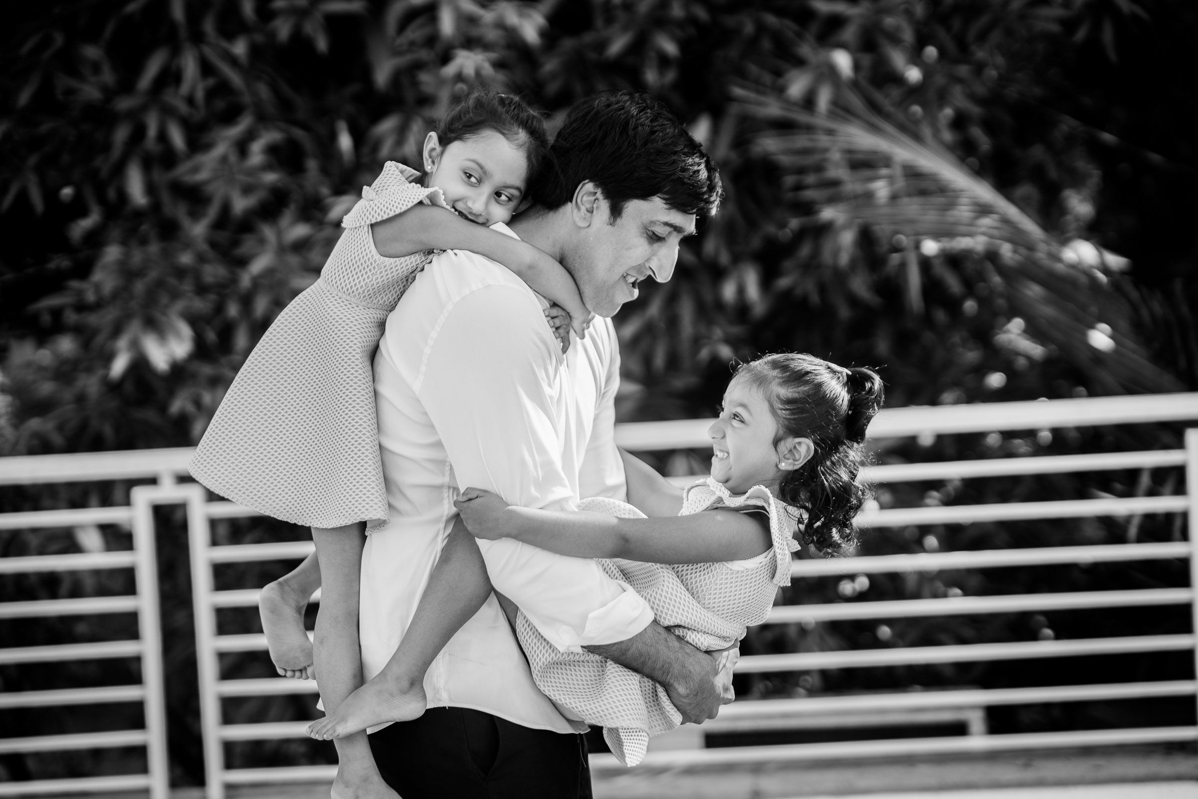 Little vows baby photogrpaher captured a beautiful family portrait of father holding his twin baby girls around him