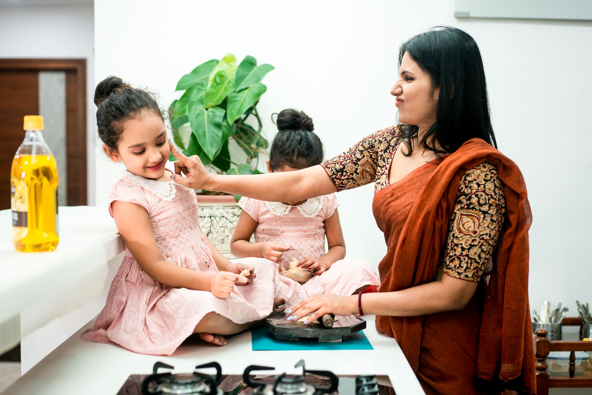 Twin baby girls playing with flour in the kitchen with their mom in hyderabad