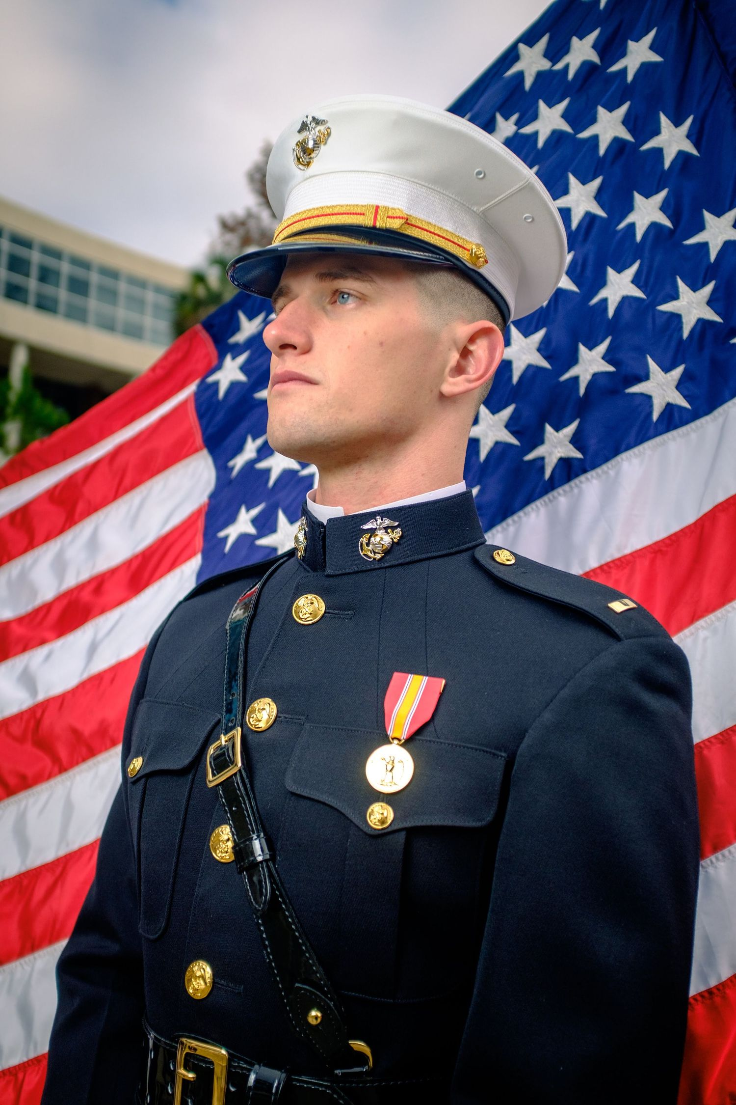 A United States Marine poses for a portrait in front of a USA flag on the University of Florida Campus.