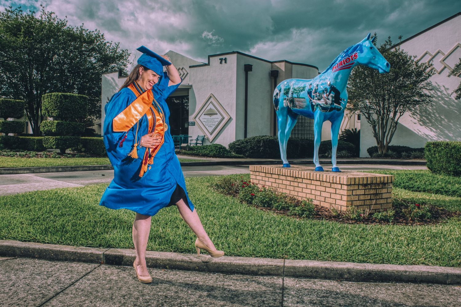 A college graduate dressed in blue is blown by the wind during a graduation photography session near Ocala Florida.