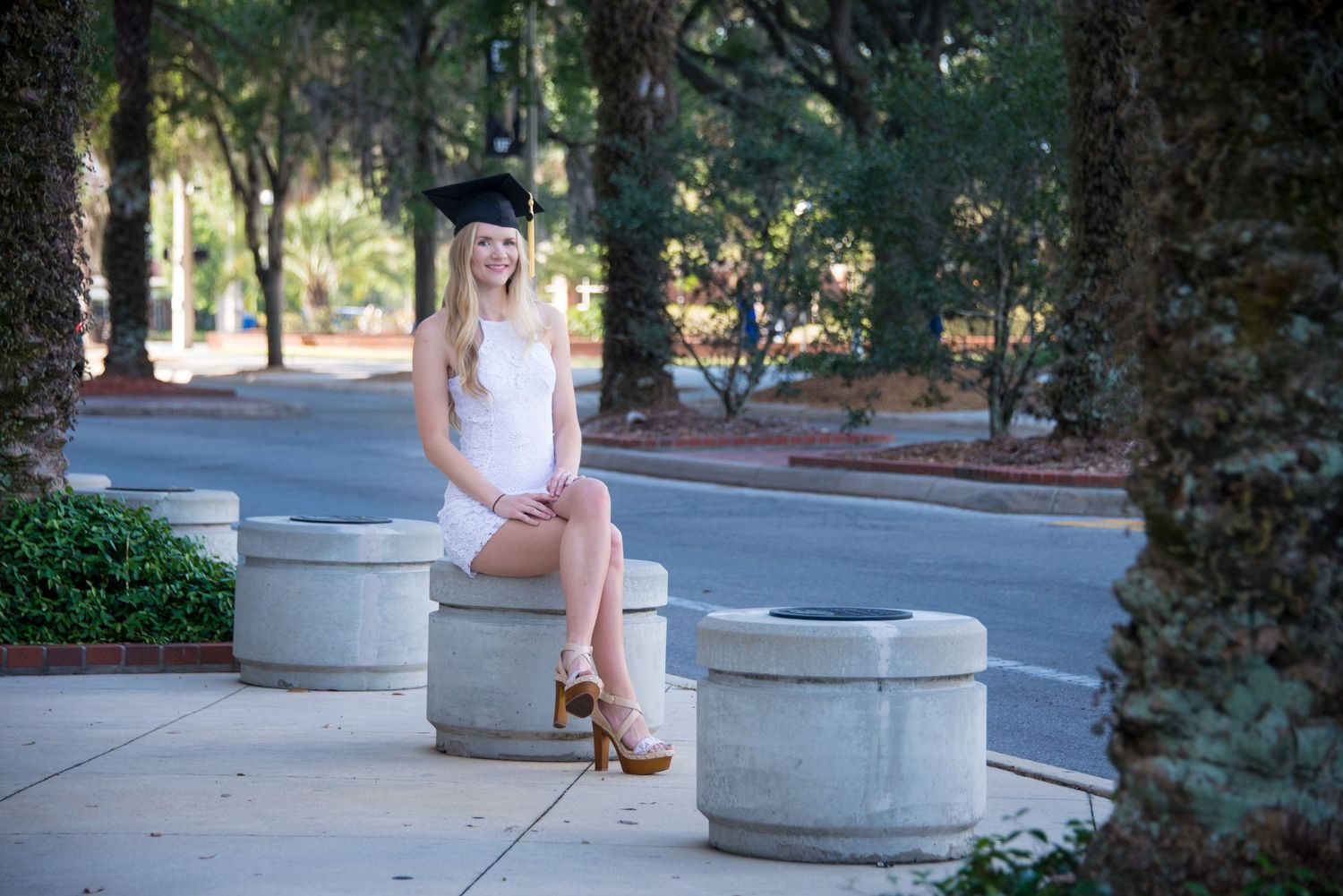A beautiful blonde woman dressed in a white dress celebrates her graduation from the University of Florida.