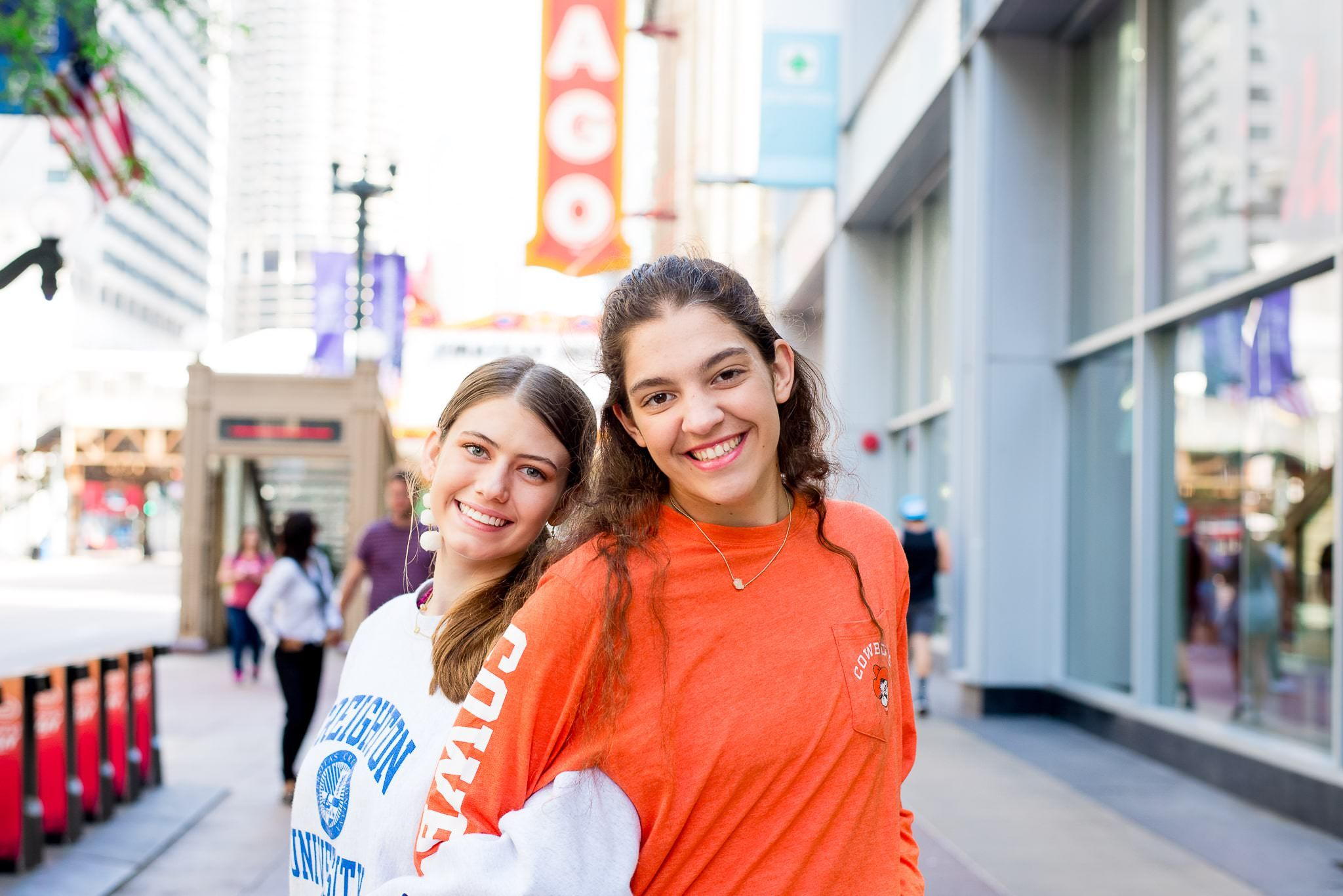 two senior girls in front of the Chicago Theater sign for Chicago senior pictures