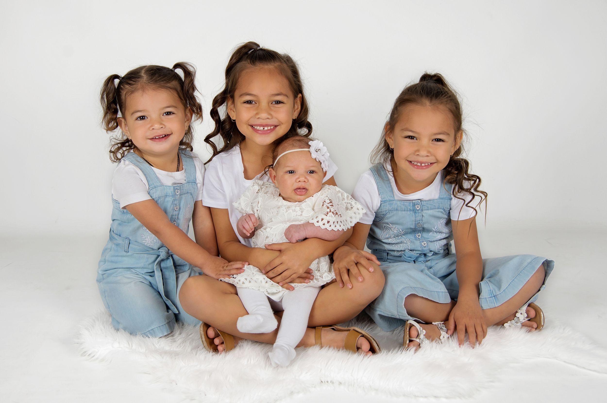 3 young girls holding baby sister smiling at camera in studio