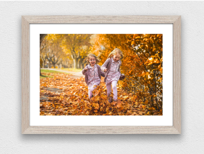 Sample framed print of two sisters running through autumn leaves